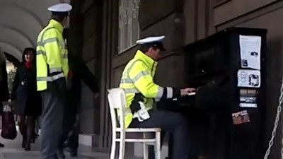 Pražský strážník hraje na pouliční piáno