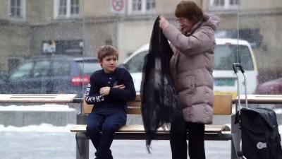 Замерзающий мальчик на остановке ждет автобус.