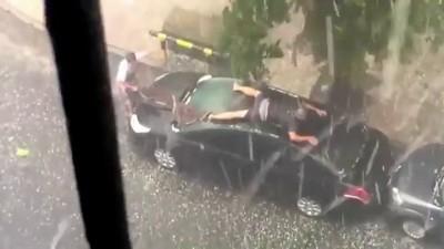 Мужик защищает машину от града