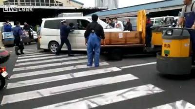Японский полицейский с дубинкой против хулигана с ножом. Рыбный рынок Цукидз ...