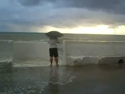 В шторм и дождь с зонтом на набережной