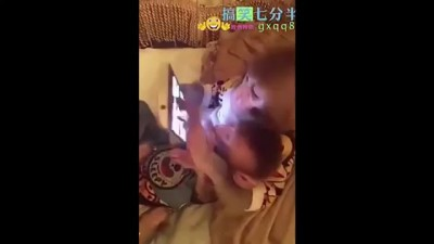Mother monkey swipes a smartphone while her baby is watcing
